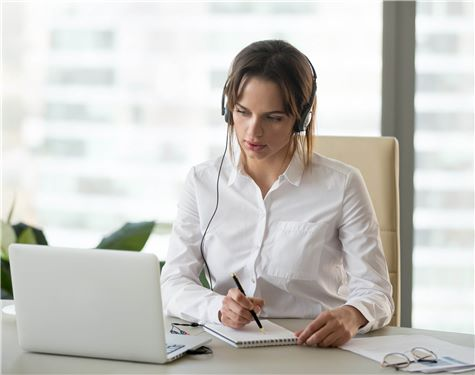 Woman at desk taking notes from laptop screen