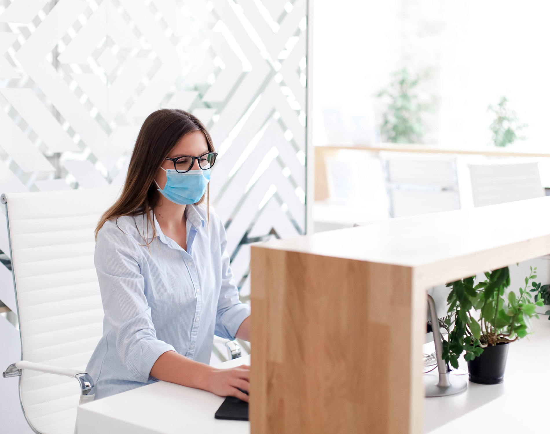 Woman wearing mask sitting at reception desk